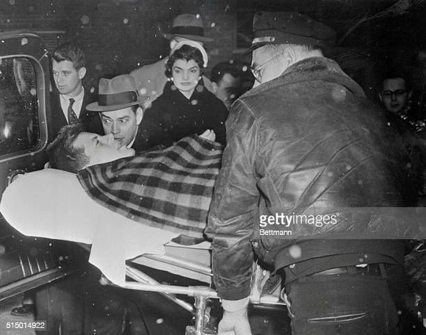 Senator John F Kennedy who was operated on for a spinal condition last October 21 is shown being lifted into an ambulance after leaving New York's...