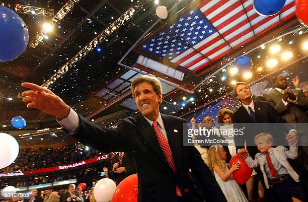 Senator John F Kerry reaches out for a balloon while John Edwards watches with son Jack Edwards and daughter Emma Claire Edwards July 29 2004 at the...