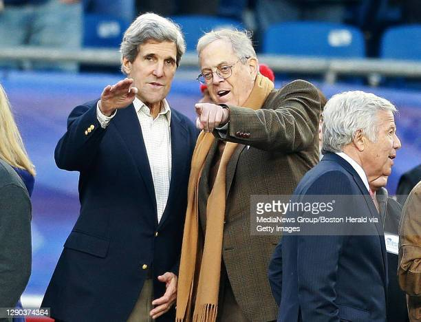 Senator John Kerry and businessman David Koch, both guests of owner Robert Kraft, right, converse before the AFC Divisional playoff game at Gillette...
