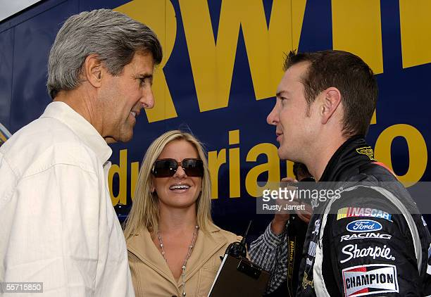 Senator John Kerry Eva Bryan and Kurt Busch driver of the Sharpie Ford talk prior to the NASCAR Nextel Cup Series Sylvania 300 on September 18 2005...