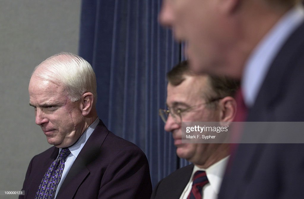 Senator John McCain (R-AZ) peacefully bows his head while Rep. Richard Gephardt (D-MO) speaks to the press about the importance of federalizing airport and airline safety.