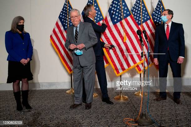 Senator John Thune , R-SD, catches the flag from falling as he passes Senate Minority Leader Mitch McConnell , R-KY, to speak with US Senator Joni...