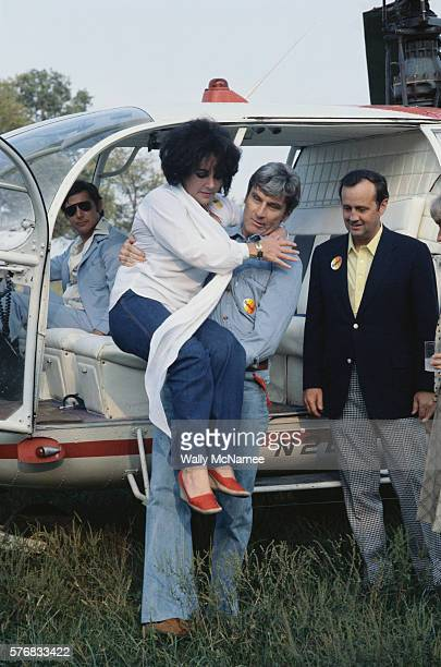 Senator John Warner lifts his wife, Elizabeth Taylor, down from a helicopter.