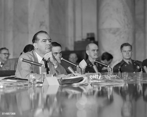 Senator Joseph McCarthy and Roy Cohn listen attentively to the testimony of Army Secretary Robert Stevens at the Senate Investigating Subcommittee...