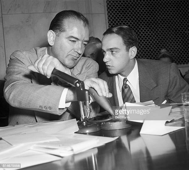 Senator Joseph McCarthy covers a microphone while Roy Cohn talks to him during a televised subcommittee meeting