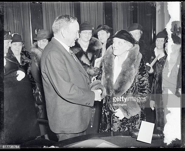 Senator Joseph T Robinson of Arkansas pictured shaking hands with Mrs Carrie Chapman Catt honorary chairman of the Cause and Cure of War Conference...