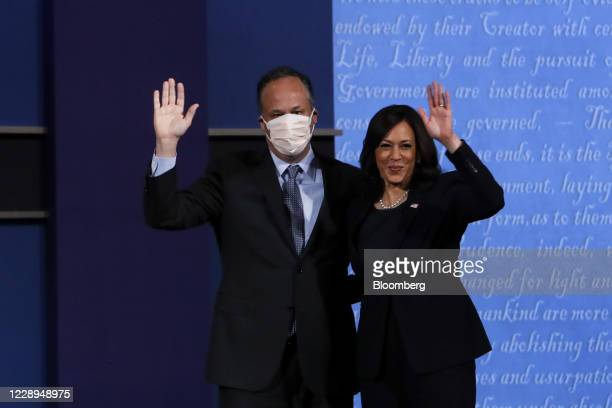 Senator Kamala Harris, Democratic vice presidential nominee, right, and husband Douglas Emhoff wearing a protective mask wave while standing on stage...