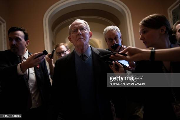 Senator Lamar Alexander walks with reporters after a meeting with Republicans about calling witnesses during the impeachment trial of US President...