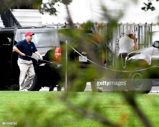 Senator Lindsey Graham left carries one of his golf clubs as he leaves the presidential limo at the White House on October 14 2017 in Washington DC...