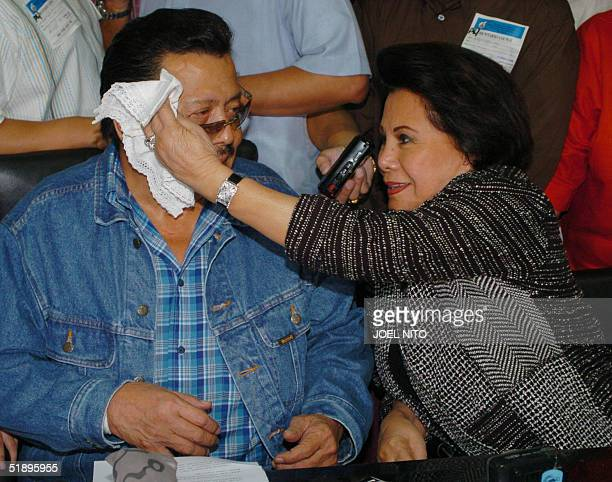 Senator Luisa 'loi' Ejercito wife of Deposed president Joseph Estrada wipe his sweat after the pressconference before boarding a flight to Hong Kong...