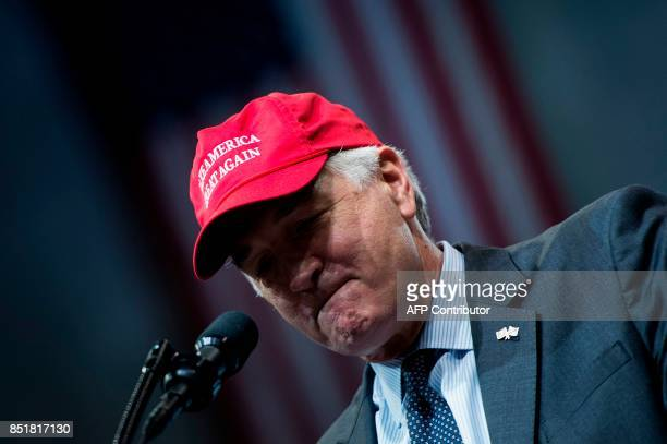 Senator Luther Strange wears a 'Make America Great Again' cap during his rally with US President Donald Trump at the Von Braun Civic Center on...