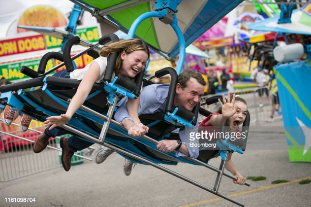 Senator Michael Bennet a Democrat from Colorado and 2020 presidential candidate rides a hanglider amusement ride with his daughters during the Iowa...