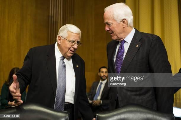 Senator Michael Enzi a Republican from Wyoming left speaks with Senate Majority Whip John Cornyn a Republican from Texas before a Senate Finance...