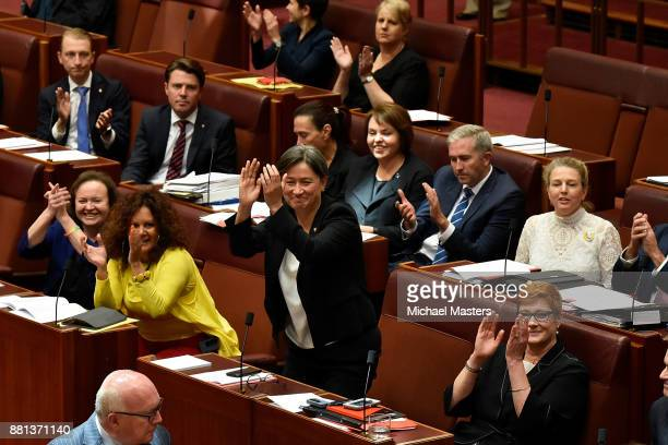 Senator Penny Wong and other Senators celebrating the resut of a vote passing the marriage eqaulity bill in the Senate at Parliament House on...