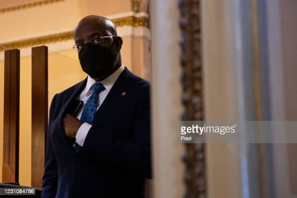 Senator Raphael Warnock stands in The Senate Reception Room corridor on the second day of former President Donald Trump's second impeachment trial at...