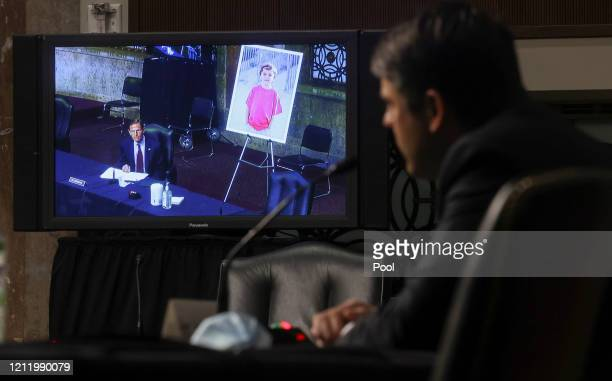 S Senator Richard Blumenthal is seen on a video monitor questioning Judge Justin Walker while Blumenthal displays a photo of a young constituent from...