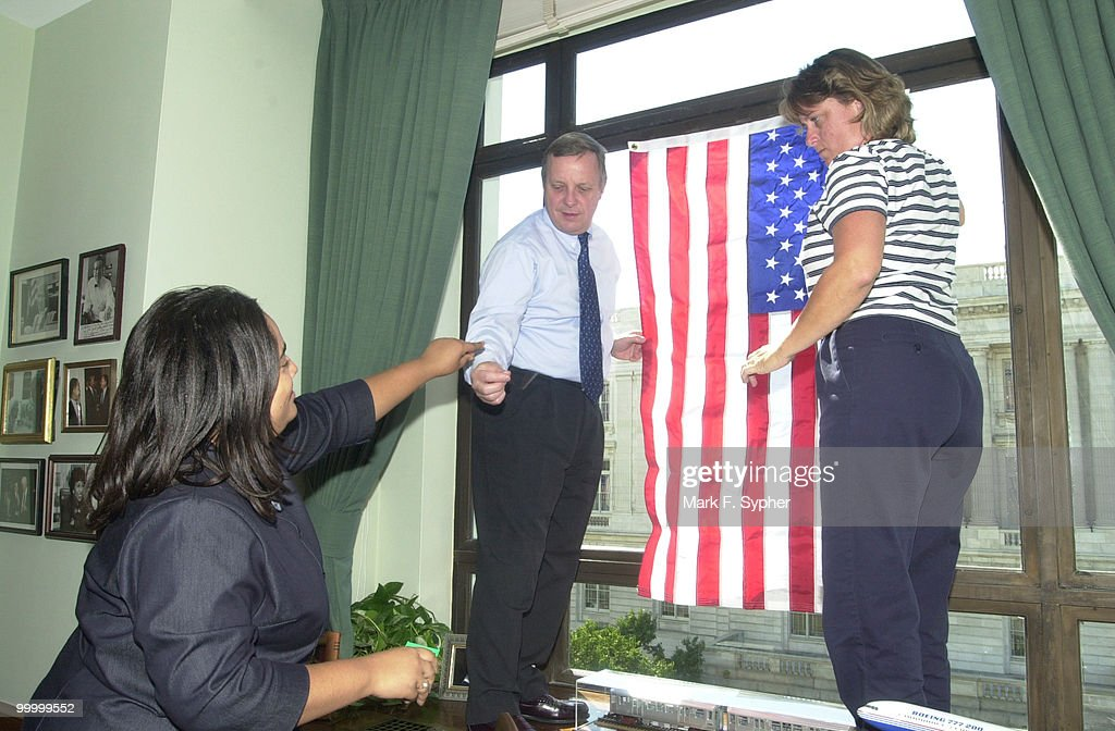 Senator Richard J. Durbin (D-IL) gets a hand from two of his staff assistants, Yolanda Turner, left, and Paula Doane, raising a flag in his personal office in the Dirksen Senate Office Building.