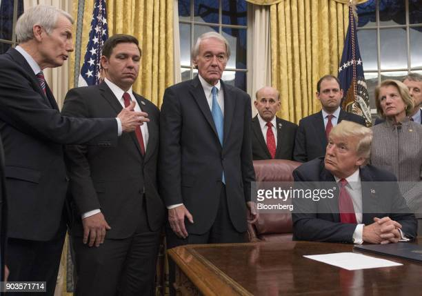 Senator Rob Portman a Republican from Ohio left speaks as US President Donald Trump seated listens before a bill signing ceremony in the Oval Office...