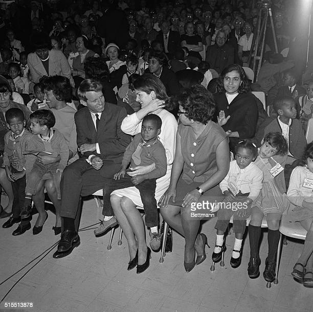 Senator Robert F Kennedy NY talks to Mrs Jacqueline Kennedy who holds fouryearold Bobby Johnson who lives at the Claremont Housing Project here at...