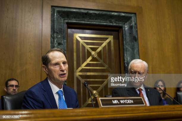 Senator Ron Wyden a Democrat from Oregon and ranking member of the Senate Finance Committee left speaks while Senator Orrin Hatch a Republican from...