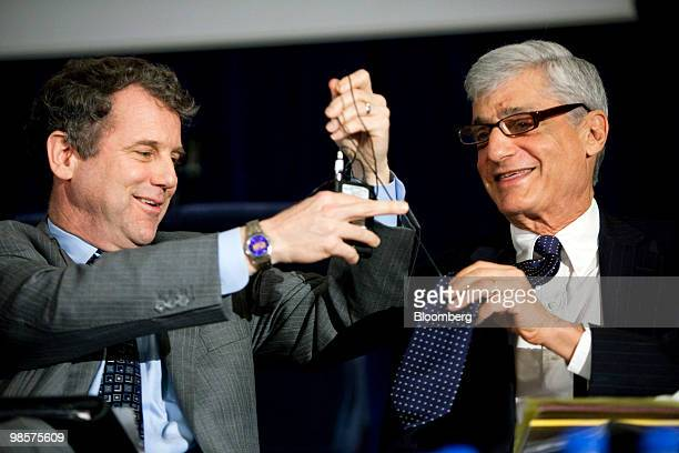 Senator Sherrod Brown a Democrat from Ohio left untangles a microphone from the tie of Robert Rubin former US treasury secretary during a panel...