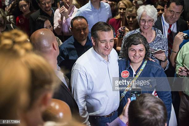 Senator Ted Cruz a Republican from Texas and 2016 presidential candidate center poses for a photograph with an attendee during a campaign event in...