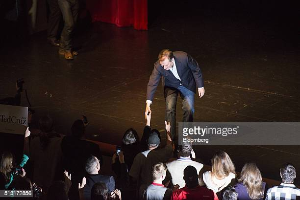 Senator Ted Cruz a Republican from Texas and 2016 presidential candidate greets attendees while on stage during a campaign event in Houston Texas US...