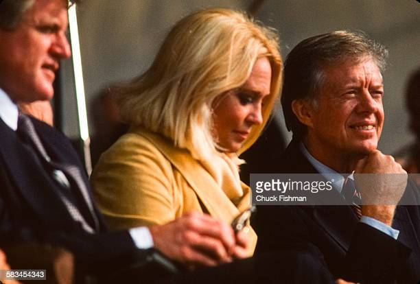 Senator Ted Kennedy left sits with his wife Joan center next to President Jimmy Carter right at the memorial dedication ceremony for the JFK Library...
