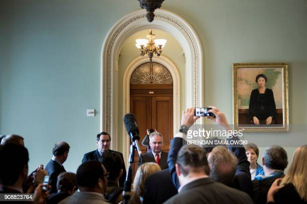 TOPSHOT Senator Tim Kaine waits to speak to reporter on Capitol Hill after the Senate voted to advance a bill financing the US government January 22...