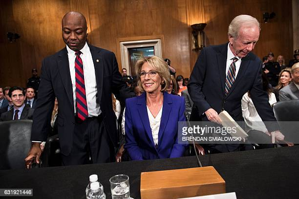 Senator Tim Scott and Joe Lieberman take seats with Betsy DeVos for her confirmation hearing for Secretary of Education before the Senate Health...