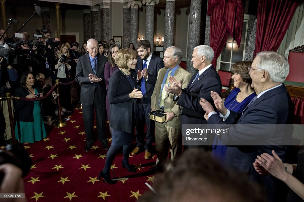 Senator Tina Smith, a Democrat from Minnesota, center, smiles after being sworn-in by U.S. Vice President Mike Pence, third right, during a mock swear-in ceremony with husband Archie Smith, center, in the Old Senate Chamber of the U.S. Capitol in Washington, D.C, U.S., on Wednesday, Jan. 3, 2018. Smith brought the number of female senators to 22 when she took the seat of former Senator Al Franken, who resigned under pressure from fellow Democrats in December following allegations of sexual misconduct. Photographer: Andrew Harrer/Bloomberg via Getty Images