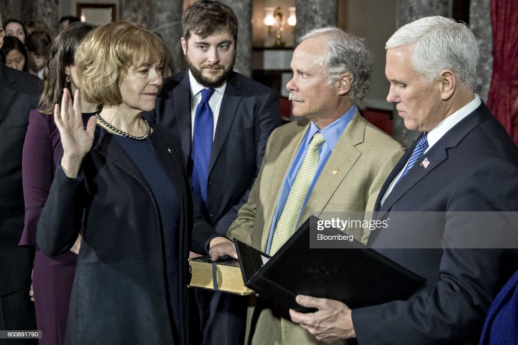 Senator Tina Smith, a Democrat from Minnesota, left, is sworn-in by U.S. Vice President Mike Pence, right, during a mock swear-in ceremony with husband Archie Smith, center, in the Old Senate Chamber of the U.S. Capitol in Washington, D.C, U.S., on Wednesday, Jan. 3, 2018. Smith brought the number of female senators to 22 when she took the seat of former Senator Al Franken, who resigned under pressure from fellow Democrats in December following allegations of sexual misconduct. Photographer: Andrew Harrer/Bloomberg via Getty Images