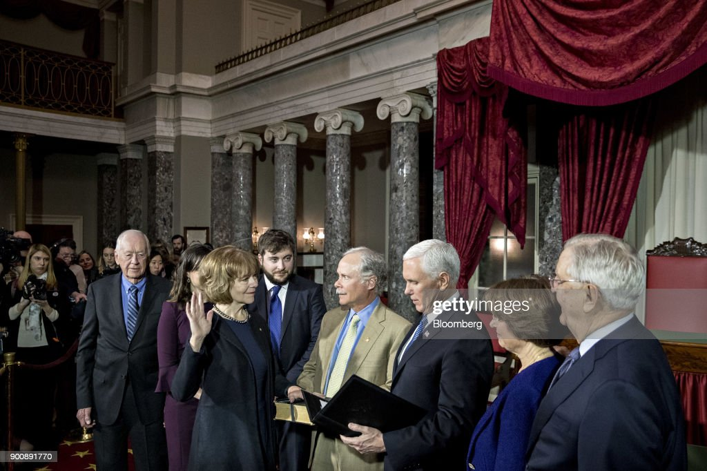 Senator Tina Smith, a Democrat from Minnesota, second left, is sworn-in by U.S. Vice President Mike Pence, third right, during a mock swear-in ceremony with husband Archie Smith, center, in the Old Senate Chamber of the U.S. Capitol in Washington, D.C, U.S., on Wednesday, Jan. 3, 2018. Smith brought the number of female senators to 22 when she took the seat of former Senator Al Franken, who resigned under pressure from fellow Democrats in December following allegations of sexual misconduct. Photographer: Andrew Harrer/Bloomberg via Getty Images