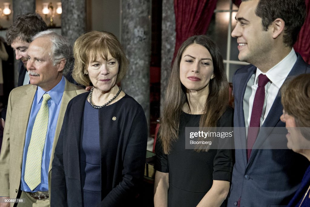 Senator Tina Smith, a Democrat from Minnesota, second left, stands during a photograph with husband Archie Smith, left, after being sworn-in by U.S. Vice President Mike Pence, not pictured, during a mock swear-in ceremony in the Old Senate Chamber of the U.S. Capitol in Washington, D.C, U.S., on Wednesday, Jan. 3, 2018. Smith brought the number of female senators to 22 when she took the seat of former Senator Al Franken, who resigned under pressure from fellow Democrats in December following allegations of sexual misconduct. Photographer: Andrew Harrer/Bloomberg via Getty Images
