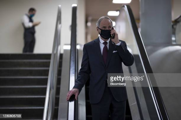Senator Tom Carper, a Democrat from Delaware, wears a protective mask while taking an escalator at the U.S. Capitol in Washington, D.C., U.S., on...