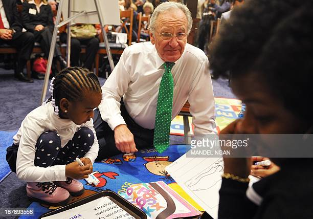 US Senator Tom Harkin DIA plays with a child before a briefing on a bipartisan proposal to expand early childhood education from birth to age 5 at...