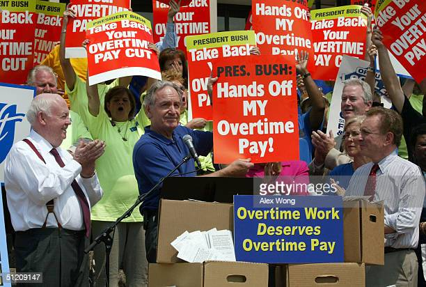 S Senator Tom Harkin holds a poster as Senator Arlen Specter and AFLCIO President John J Sweeney look on during a rally to protest the Bush...