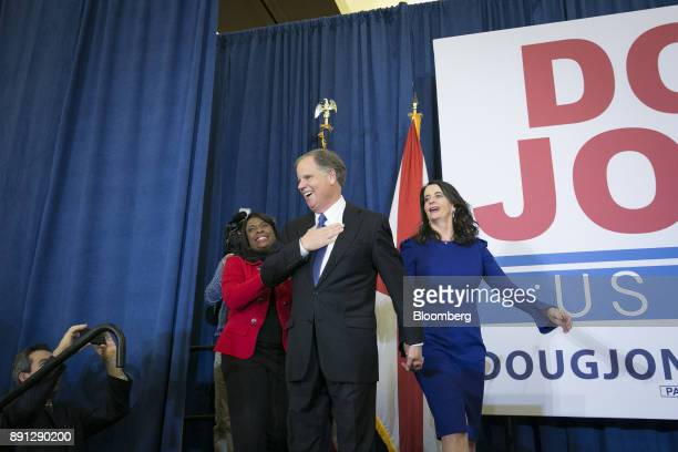 Senatorelect Doug Jones a Democrat from Alabama center and wife Louise Jones right greet the audience at an election night party in Birmingham...