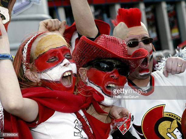 Senators fans Bryanna, Brian and Steve Lester pump up the crowd at the Party Plaza outside of Scotiabank Place before the Ottawa Senators take on the...