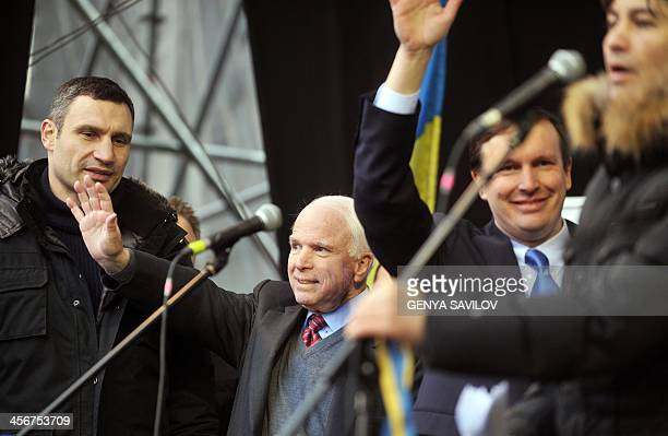 US Senators John McCain and Chris Murphy wave to protestors as Ukrainian UDAR party's leader Vitali Klitschko looks on during a mass rally of the...