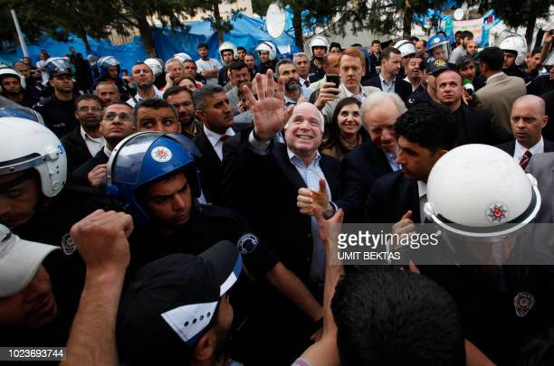 US Senators John McCain and Joseph Lieberman greet Syrian refugees during their visit at Yayladagi refugee camp in Hatay province on the...
