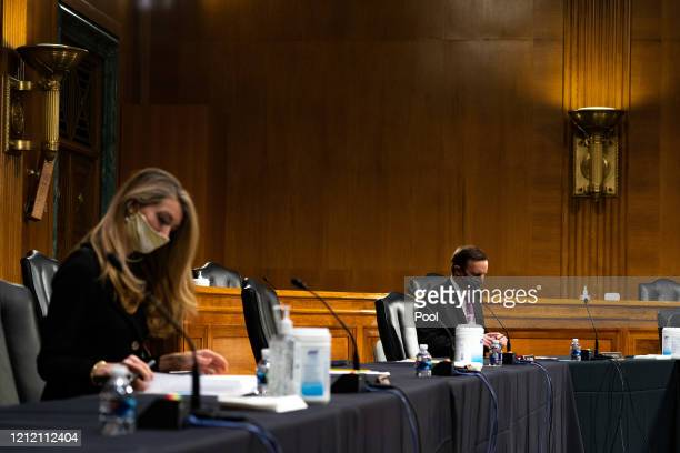 Senators Kelly Loeffler RGa and Chris Murphy DConn look at their notes during a Senate Health Education Labor and Pensions Committee hearing on new...
