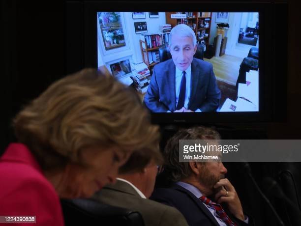 Senators listen to Dr. Anthony Fauci, director of the National Institute of Allergy and Infectious Diseases speak remotely during a Senate Health,...