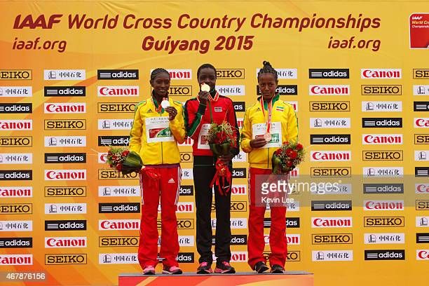 Senbere Teferi of Ethiopia Agnes Jebet Tirop of Kenya and Netsanet Gudeta of Ethiopia pose on the podium after the senior women's race at the IAAF...
