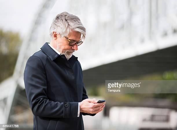 sending an sms with a smart phone on the street. - 50 59 years stock pictures, royalty-free photos & images