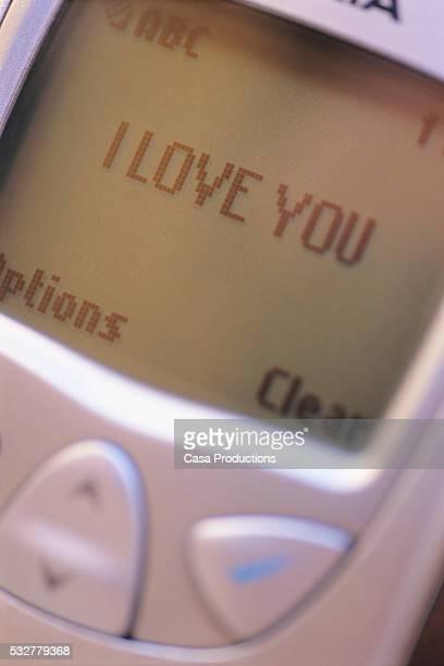 sending messages of love on cellular telephone - casa stock-fotos und bilder