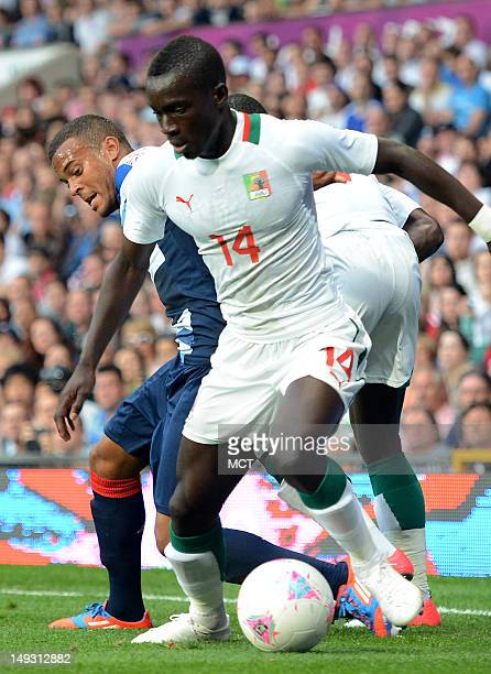 Senegal midfielder Idrissa Gueye defends his possession of the ball against British defender Ryan Bertrand left in the first half of a Group A match...