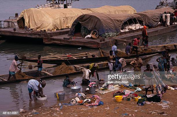 Senegal Niger River Women washing clothes in river from bank with barges and wooden canoes transporting soil and other goods behind
