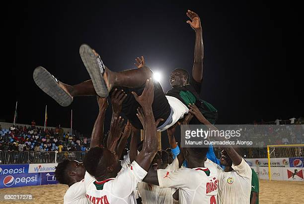 Senegal players lift head coach Oumar Sylla after winning the CAF Beach Soccer Africa Cup of Nations final match between Senegal and Nigeria at EKO...