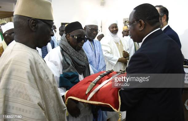 Senegal President Macky Sall presents the sword El Hadj Omar Saidou Tall during a ceremony with French Prime Minister Edouard Philippe at the Palace...